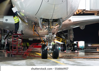 Pre-flight service of modern passenger aircraft in the night airport. The main landing gear close up. The plane is parked on the airport apron.