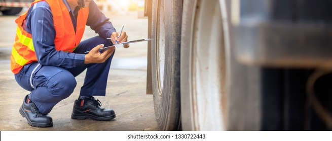 Preforming a pre-trip inspection on a truck,Concept preventive maintenance truck checklist,Truck driver holding clipboard with checking of truck.