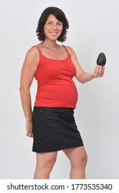 pregnan woman holding a avocado on white background