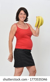pregnan woman holding a banana on white background