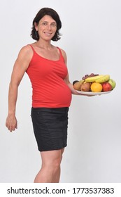 pregnan woman holding a group of fruits on white background