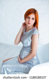 Pregnancy beauty. Beautiful elegant readhead pregnant woman in white dress posing in tender home interior.
