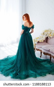 Pregnancy beauty. Beautiful elegant readhead pregnant woman in green dress posing in tender home interior.