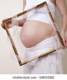 Pregnancy Concept - Pregnant Belly with a picture frame and pink ribbon
