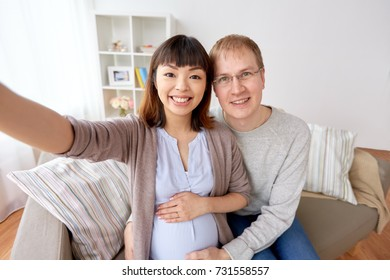 pregnancy, family and people concept - happy pregnant woman with husband taking selfie at home