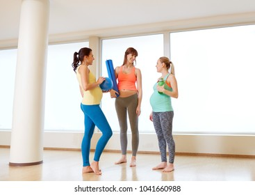 pregnancy, fitness and healthy lifestyle concept - group of happy pregnant women with sports equipment talking in gym