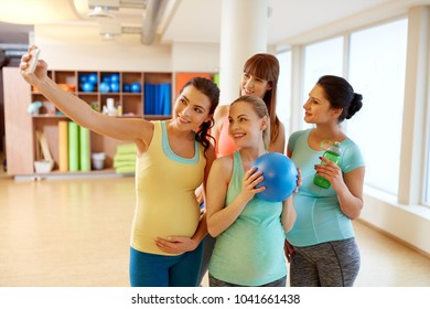 pregnancy, fitness and healthy lifestyle concept - group of happy pregnant women with sports stuff taking selfie by smartphone in gym