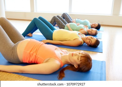 pregnancy, fitness and healthy lifestyle concept - group of pregnant women lying on mats in gym