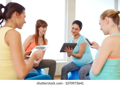 pregnancy, fitness and technology concept - group of happy pregnant women with tablet pc computers and smartphone sitting on exercise balls in gym