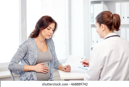 pregnancy, gynecology, medicine, health care and people concept - gynecologist doctor with prescription and pregnant woman meeting at hospital