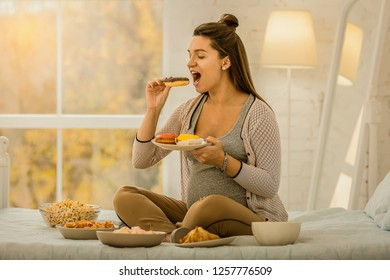 The pregnancy habits. A woman eating a lot while pregnancy