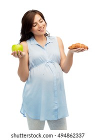 pregnancy, healthy eating, junk food and people concept - happy pregnant woman choosing between green apple and croissant over white background