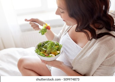 pregnancy, healthy food and people concept - close up of happy pregnant woman eating vegetable salad for breakfast in bed at home