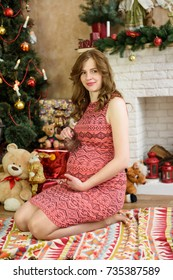 pregnancy, holiday, people and expectation concept - happy pregnant woman sitting  and touching her belly at home over christmas tree background