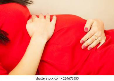 Pregnancy, motherhood and happiness concept. elegant pregnant woman in red dress relaxing on sofa and touching her belly. Part of body