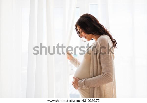 grossesse, maternité, personnes et concept d'attente - gros plan sur une femme enceinte heureuse avec un gros ventre à la fenêtre