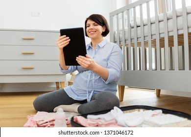 pregnancy, nursery and people concept - happy pregnant middle-aged woman using tablet computer packing bag or suitcase for maternity hospital at home