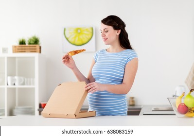 pregnancy, people and junk food concept - happy pregnant woman eating pizza at home kitchen