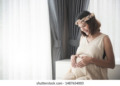 Pregnancy, Pregnant woman touch big belly in Maternity Dresses sitting near window at home. happiness of motherhood preparation and expectation with copy space concept.