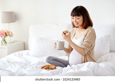 pregnancy, rest, people and breakfast concept - happy pregnant asian woman with cup drinking tea and eating cookie in bed at home bedroom