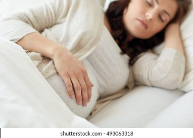 pregnancy, rest, people and expectation concept - pregnant woman sleeping in bed at home