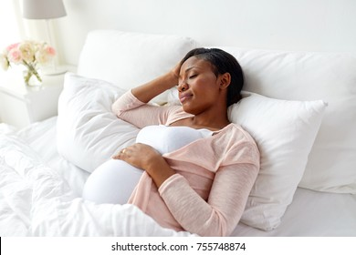 pregnancy, rest, people and expectation concept - pregnant african american woman sleeping in bed at home