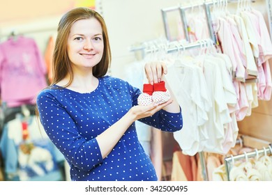 Pregnancy shopping. Portrait of young pregnant woman choosing newborn clothes at baby shop store