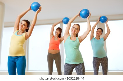 pregnancy, sport, fitness and healthy lifestyle concept - group of happy pregnant women training with small exercise balls in gym