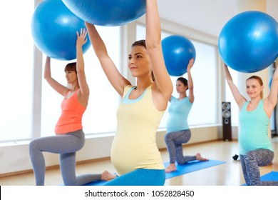 pregnancy, sport, fitness and healthy lifestyle concept - group of happy pregnant women training with exercise balls in gym