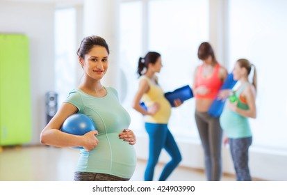 pregnancy, sport, fitness, people and healthy lifestyle concept - happy pregnant woman with ball in gym