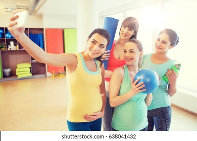 pregnancy, sport, fitness, people and healthy lifestyle concept - group of happy pregnant women with sports stuff taking selfie by smartphone in gym