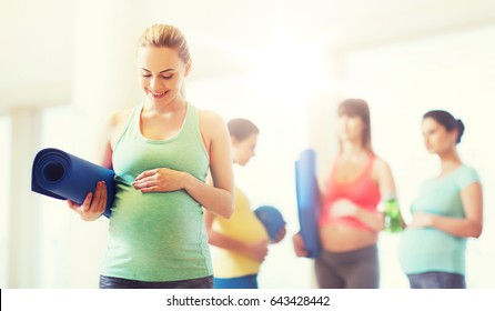pregnancy, sport, fitness, people and healthy lifestyle concept - happy pregnant woman with mat in gym