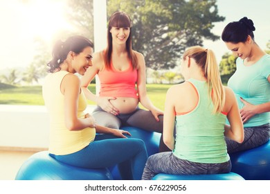 pregnancy, sport, fitness, people and healthy lifestyle concept - group of happy pregnant women sitting and talking on balls in gym