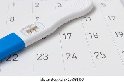 Pregnancy test on calendar background, health care concept