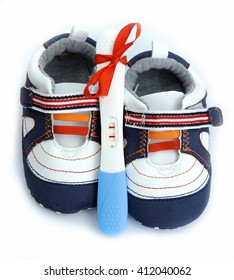 pregnancy test positive result with baby shoes and present red ribbon on blue background