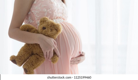 Pregnancy woman  in pink dress holding a teddy bear  on the bed in bedroom.