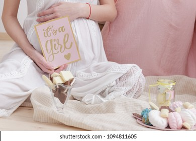 "pregnancy woman in white dress sitting on the floor at the celebration baby shower party.she holds a postcard with the inscription ""this is a girl"".pregnancy, motherhood concept."