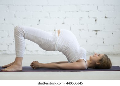 Pregnancy Yoga and Fitness concept. Portrait of young pregnant yoga model working out indoors. Pregnant happy fitness person enjoy yoga practice at home. Prenatal shoulder bridge exercise. Full length