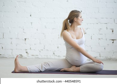 Pregnancy Yoga and Fitness concept. Portrait of young pregnant yoga model working out indoors. Pregnant fitness person practicing yoga at home. Prenatal gentle spinal twist in Janu Sirsasana pose
