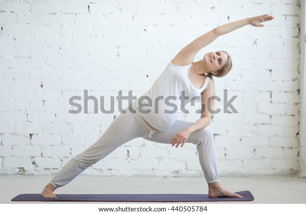 Pregnancy Yoga and Fitness concept. Portrait of beautiful young pregnant yoga model working out indoor. Pregnant happy fitness person enjoying yoga practice at home. Prenatal extended side angle pose