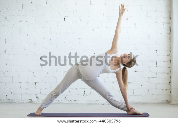 Pregnancy Yoga and Fitness concept. Portrait of beautiful young pregnant yoga model working out indoor. Pregnant happy fitness person practicing yoga at home. Prenatal Utthita Trikonasana pose