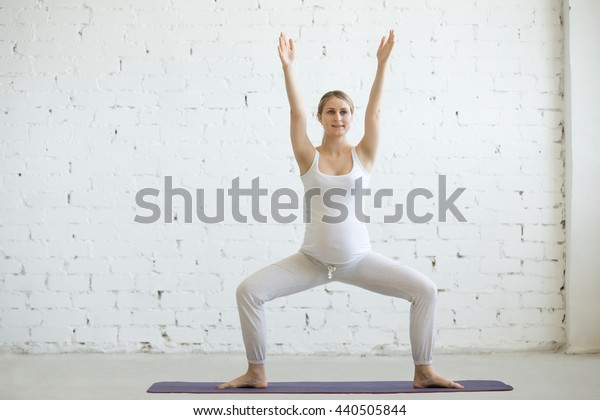 Pregnancy Yoga and Fitness concept. Portrait of beautiful young pregnant yoga model working out indoor. Pregnant happy fitness person enjoy yoga practice at home. Prenatal Goddess or Sumo Squat Pose