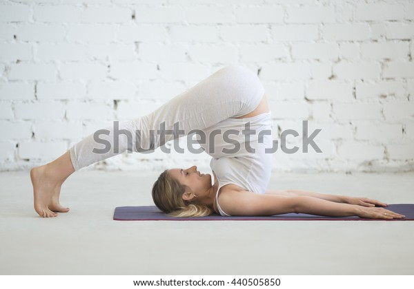 Pregnancy Yoga and Fitness concept. Portrait of young pregnant yoga model working out indoors. Pregnant happy fitness person practicing yoga at home. Prenatal halasana, plough (yin snail) pose