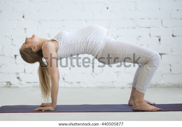 Pregnancy Yoga and Fitness concept. Portrait of young pregnant yoga model working out indoors. Pregnant happy fitness person practicing yoga at home. Prenatal Table Top Pose. Full length