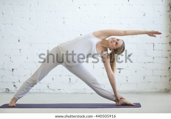 Pregnancy Yoga and Fitness concept. Portrait of beautiful young pregnant yoga model working out indoor. Pregnant happy fitness person enjoying yoga practice at home. Prenatal Extended Triangle pose