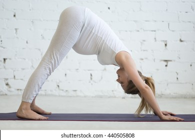 Pregnancy Yoga and Fitness. Portrait of young pregnant yoga model working out in loft. Pregnant fitness person practicing yoga at home and smiling with closed eyes. Prenatal downward-facing dog pose