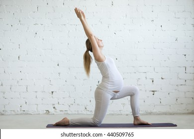 Pregnancy Yoga and Fitness. Young pregnant yoga model working out in loft interior with white walls. Pregnant fitness person practicing yoga exercises at home. Prenatal variation of Warrior I posture