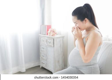 pregnant asian female use tissue paper close her mouth and nose, she cough and feeling fever, pregnancy promotion healthcare, influenza immunization