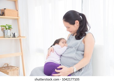 Pregnant asian mother breast feeding her daughter at home