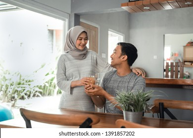 pregnant asian muslim woman offering some drink to her husband in the kitchen